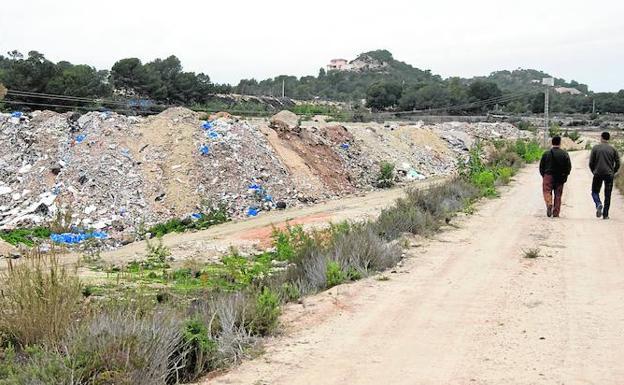 Dos vecinos pasean y observan en 2010 el estado del macrovertedero que llevaba seis años en una zona de la población alicantina de San Miguel de Salinas ante la permisividad institucional. / ALBERTO ARAGÓN